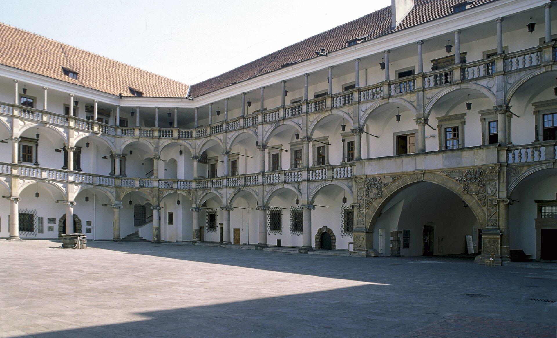 """Renesansowy, krużgankowy dziedziniec zamku wBrzegu.Książę Jerzy II zrodu Piastów wpoł. XVI w. dokonał przebudowyswojej siedziby wBrzegu wstylu renesansowym. Wzorem była dla niego przebudowa Wawelu przez Jagiellonów. Podobieństwa spowodowały nadanie zamkowi brzeskiemu miana """"Śląskiego Wawelu"""". Prace kontynuowali kolejni Piastowicze na tronie księstwa: Fryderyk II iJerzy II. Wlatach 1554-1560 wzniesiono reprezentacyjną bramę wjazdową ozdobioną posągami fundatora ijego małżonki oraz popiersiami swoich przodków. Renesansowy, krużgankowy dziedziniec zamku wBrzegu.Książę Jerzy II zrodu Piastów wpoł. XVI w. dokonał przebudowyswojej siedziby wBrzegu wstylu renesansowym. Wzorem była dla niego przebudowa Wawelu przez Jagiellonów. Podobieństwa spowodowały nadanie zamkowi brzeskiemu miana """"Śląskiego Wawelu"""". Prace kontynuowali kolejni Piastowicze na tronie księstwa: Fryderyk II iJerzy II. Wlatach 1554-1560 wzniesiono reprezentacyjną bramę wjazdową ozdobioną posągami fundatora ijego małżonki oraz popiersiami swoich przodków. Źródło: Jerzy Strzelecki, Wikimedia Commons, licencja: CC BY-SA 3.0."""
