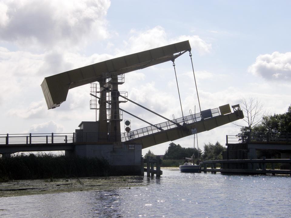 Fotografia prezentuje podniesione ramię mostu zwodzonego pod, którym przepływa żaglówka.