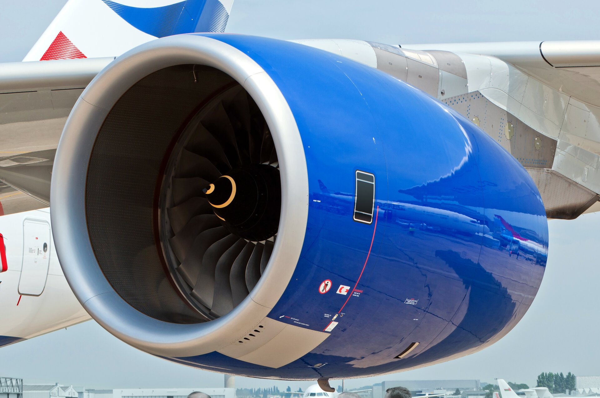 Zdjęcie przedstawia silnik odrzutowy na skrzydle samolotu pasażerskiego. Kadłub pomalowany jest na kolory biały iniebieski, natomiast wnętrze turbiny jest czarne zfantazyjną pomarańczową spiralą na samym czubku osi tak zwanego wentylatora, czyli przedniej obracającej się części.