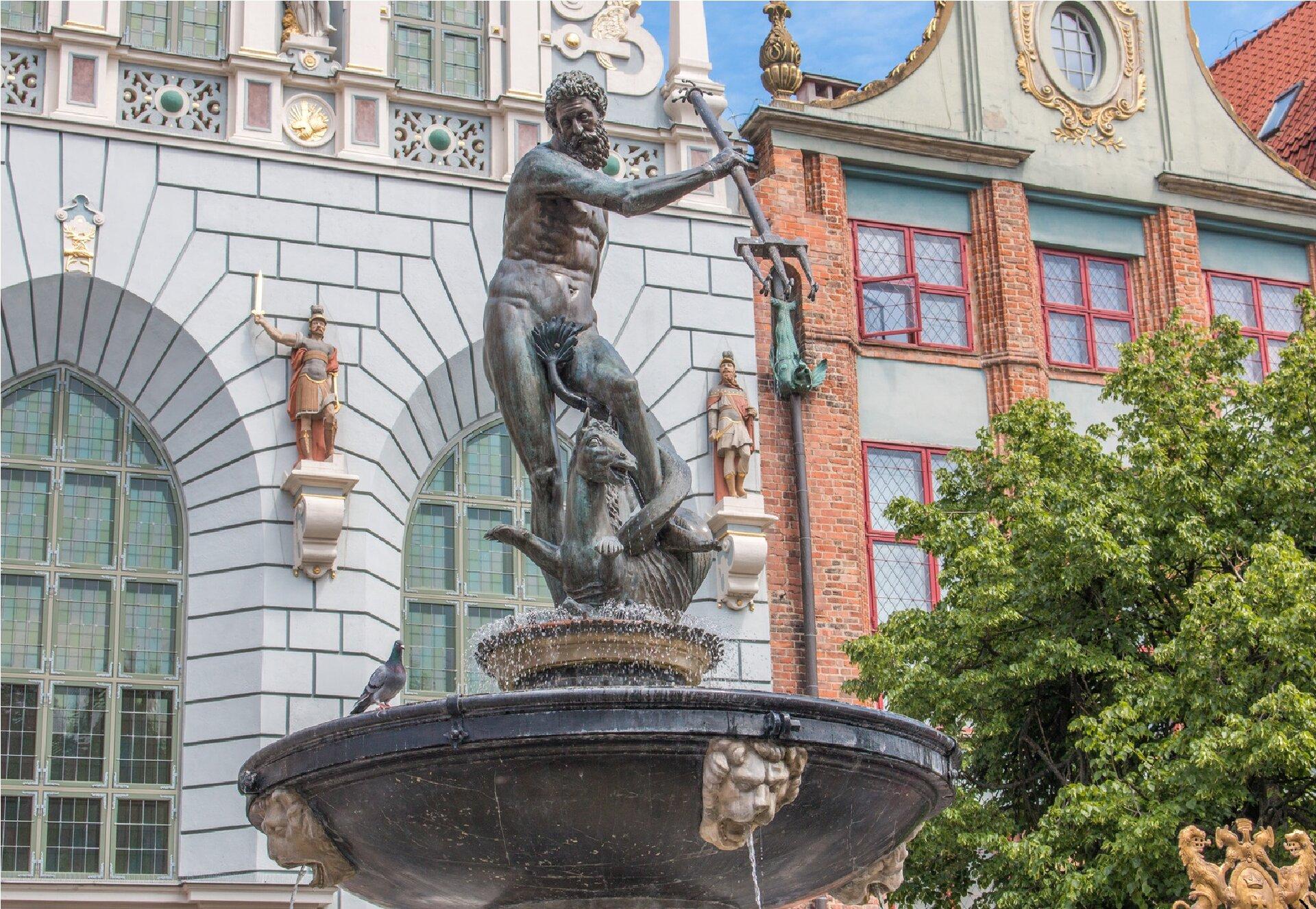 Ilustracja przedstawia Fontannę Neptuna wGdańsku. Wcentrum fontanny ustawiona jest rzeźba zbrązu ukazująca nagiego, brodatego mężczyznę ztrójzębem wprawej wysuniętej do przodu ręce. Władca mórz został ukazany podczas walki zkońmi morskimi, które wiją się ujego stóp. Dynamicznie przedstawiona postać została wykonana zdużą dbałością odetal. Na jego ciele zpieczołowitością wyrzeźbiono każdy mięsień. Pod rzeźbą znajduje się górna, czarna misa fontanny zjasnymi głowami lwów, zktórych leje się woda. Posąg ukazany został na tle Toruńskich kamieniczek.