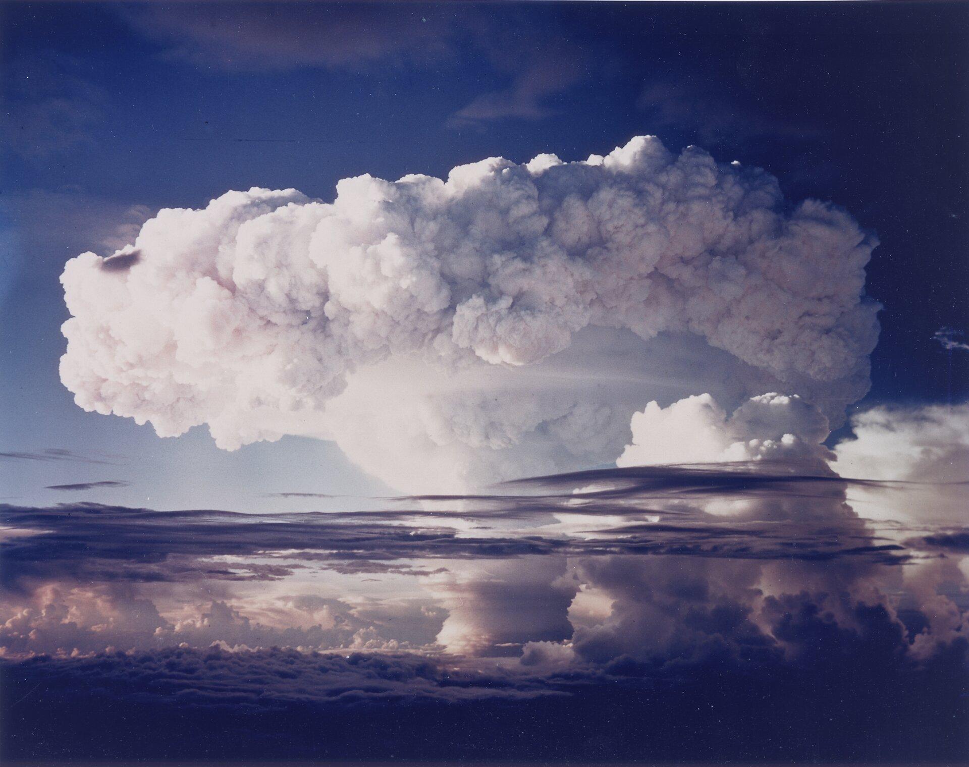 Kolorowe zdjęcie 6: Ivy Mike, próba jądrowa nad oceanem. Zdjęcie przedstawia białą chmurę tworzącą grzyb atomowy. Górna część grzyba to kłęby białych chmur ułożonych wkrąg.