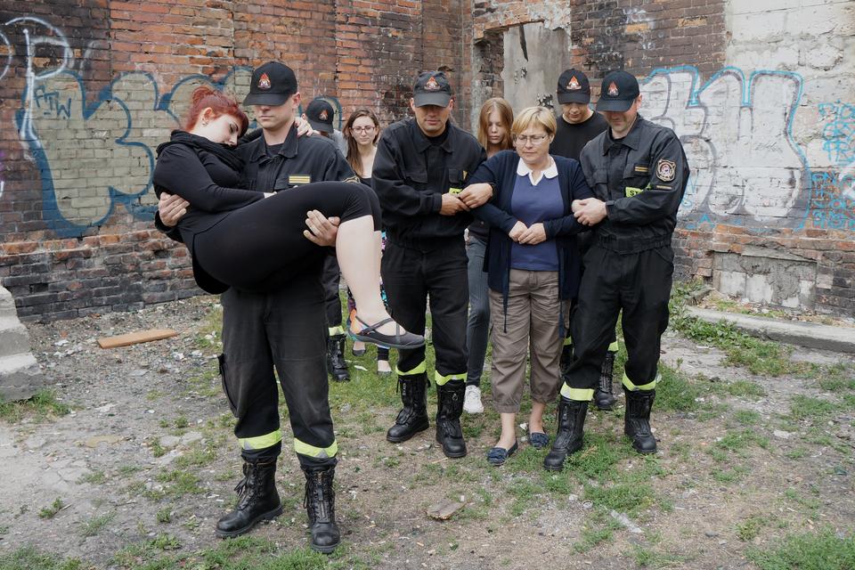 Zdjęcie przedstawia ewakuację osób zbudynku. Dzień. Pięciu ratowników pomaga czterem kobietom wopuszczeniu niebezpiecznego miejsca. Ratownicy ubrani wczarne spodnie, kurtki, czapki zdaszkiem oraz czarne wysokie buty. Nad butami pozioma odblaskowa zielonkawa opaska. Pierwszy ratownik niesie kobietę. Kobieta bokiem ułożona wpozycji siedzącej na rękach ratownika. Ztyłu dwaj ratownicy prowadzą pod rękę starszą kobietę. Strażacy idą prowadząc kobietę pomiędzy sobą. Wtle dwaj strażacy pomagają pozostałym kobietom prowadząc je pod rękę. Wokół podwórza wysokie ceglane mury budynków.