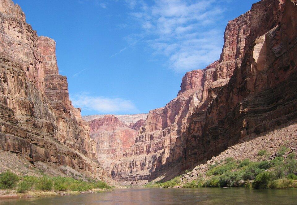 Na zdjęciu głęboki kanion obardzo stromych ścianach. Wdnie doliny rzeka. Brzegi porośnięte niską roślinnością.