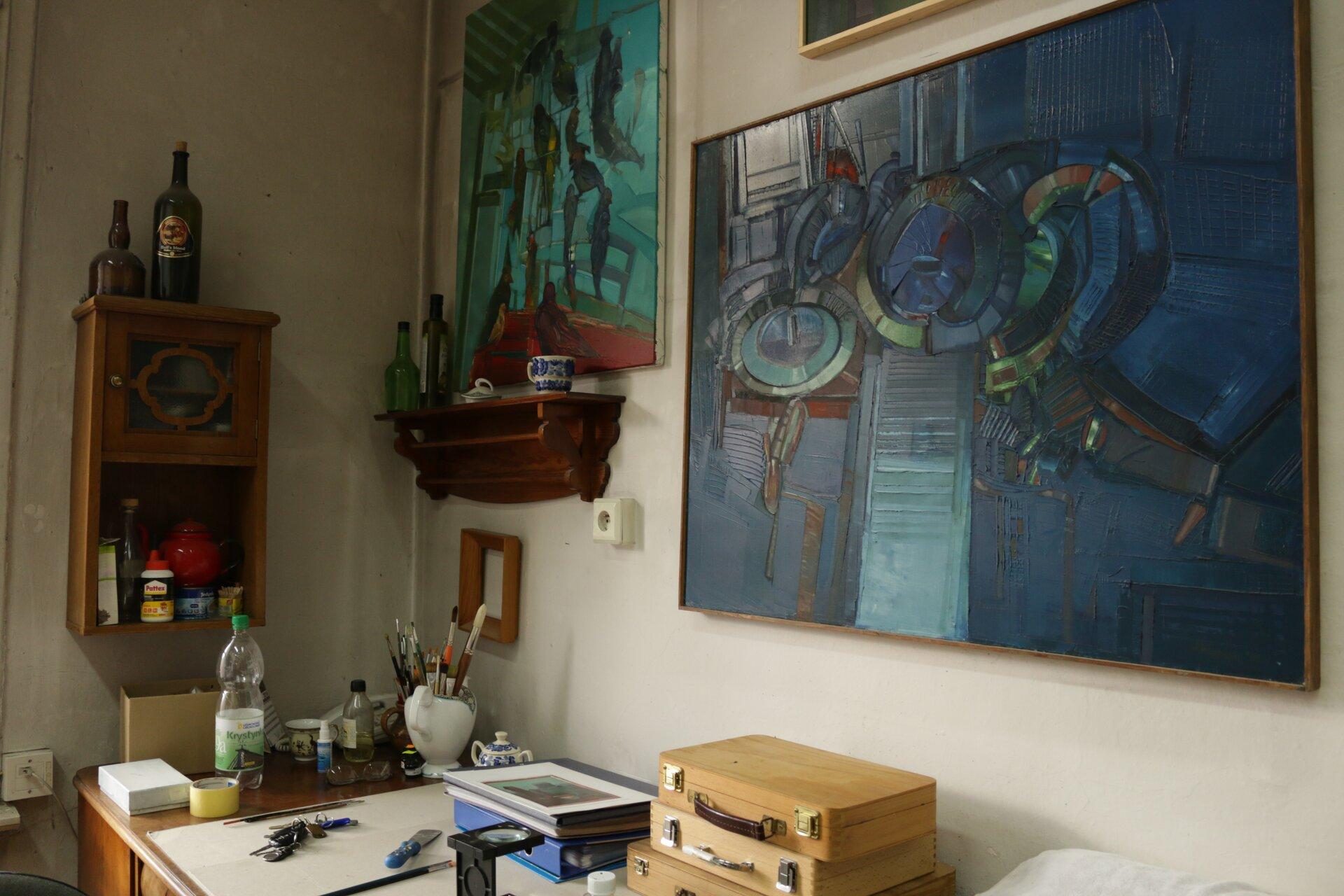 Ilustracja przedstawia fragment wnętrza pracowni malarskiej. Na zdjęciu znajduje się biurko, na którym ustawione są buteleczki, dwa dzbanki służąca za pojemniki na pędzle, segregatory, lupa, skrzynki na farby taśma klejąca oraz przedmioty użytku codziennego. Część biurka przykryta jest jasną tekturą. Nad biurkiem wiszą dwie drewniane szafki oraz dwa abstrakcyjne obrazy.