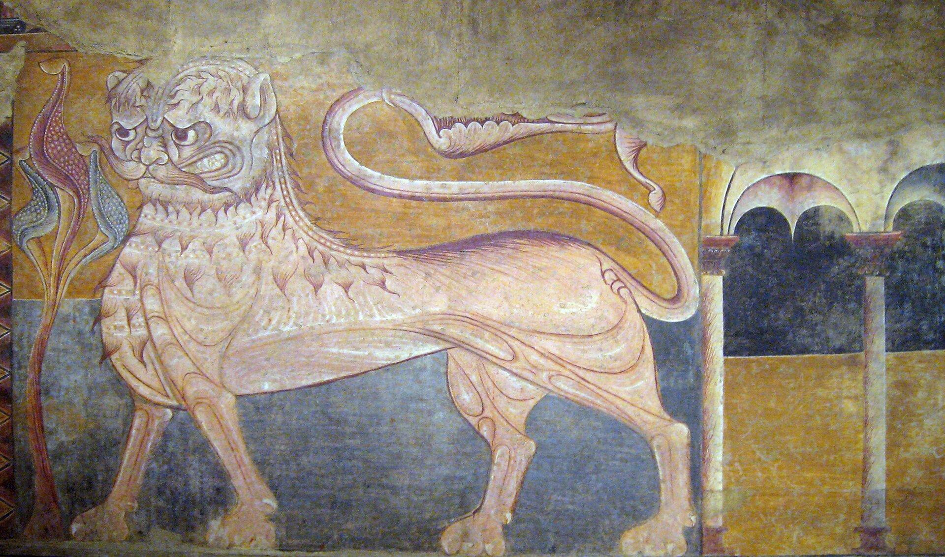 """Ilustracja interaktywna przedstawia fresk """"Lew"""", znajdujące się wklasztorze wCastile-León wHiszpanii. Malowidło ukazuje jasno-beżową postać zwierzęcia kroczącego na czterech łapach zdługim, podwiniętym go góry ogonem. Zmarszczone brwi, wyszczerzone zęby inastroszone, szpiczaste uszy wyrażają złość. Pod niemal ludzkim zwyglądu nosem artysta namalował wąsy. Ciało tytułowego """"lwa"""" pokryte jest kępkami włosów. Twurcy udało się oddać rysunek mięśni zwierzęcia. Postać ukazana jest na żółto-błękitnym tle. Po jego lewej stronie znajduje się roślina oczerwono-niebieskich liściach, natomiast po prawej fragment architektury: dwie kolumny złukowym sklepieniem. Górna część fresku jest zniszczona. Dominującymi kolorami malowidła jest żółć iniebieski."""