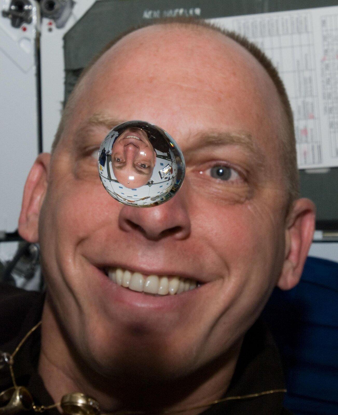 Zdjęcie przedstawia kroplę wody wstanie nieważkości. Na pierwszy planie widoczna kropla wody. Kształt zbliżony do kuli. Średnica około dwóch centymetrów. Wtle twarz mężczyzny. Mężczyzna łysiejący. Niebeskie oczy, jasne brwi. Szeroki uśmiech. Wzrok skierowany ku kropli, która utrzymuje się na wysokości jego oczu. Odległość kropli od twarzy mężczyzny wynosi około kilkunastu centymetrów.