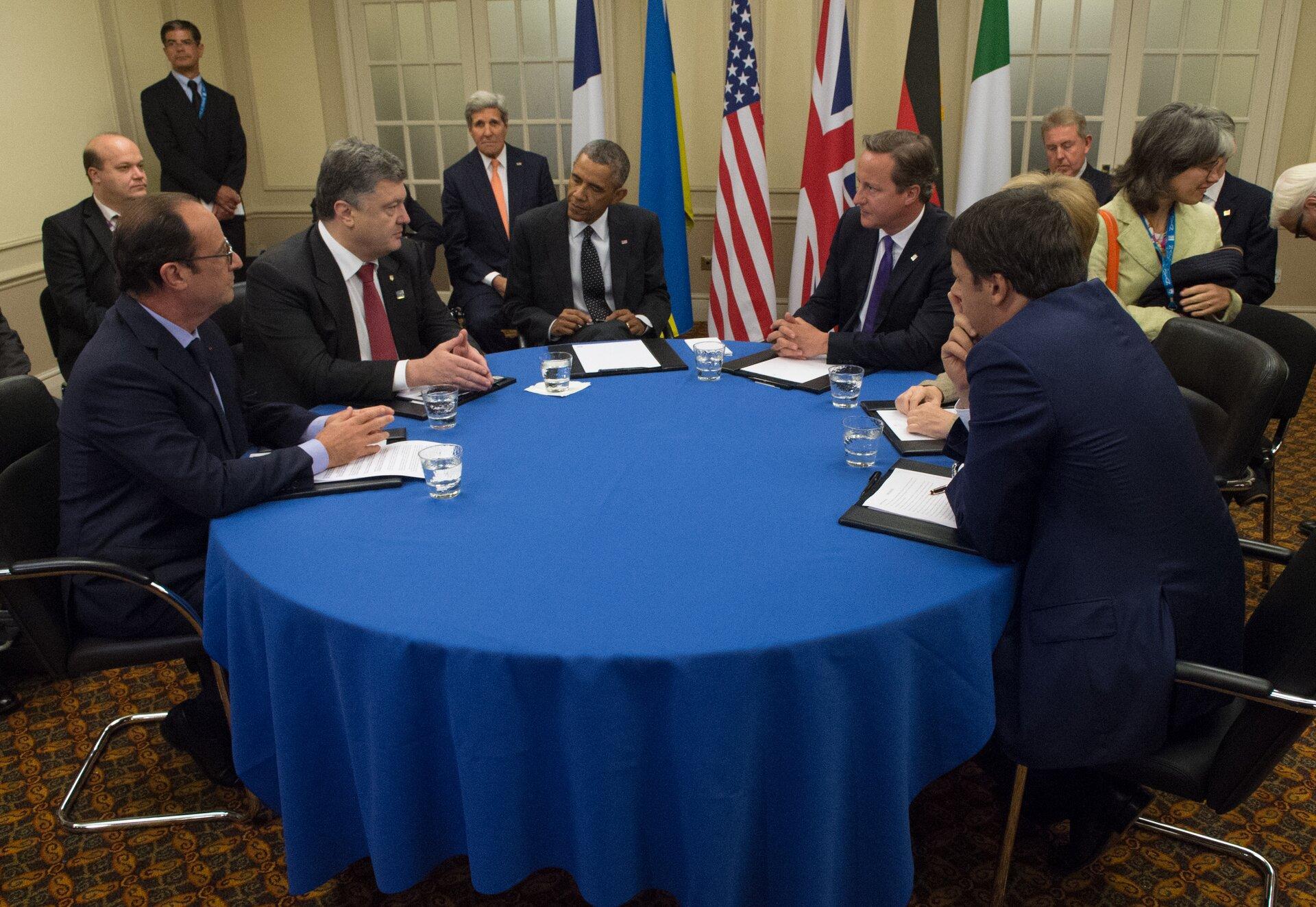 Na zdjęciu okrągły stół nakryty niebieskim suknem. Od lewej strony siedzą przy stole prezydent Francji François Hollande, prezydent Ukrainy Petro Poroszenko, prezydent Stanów Zjednoczonych Barack Obama, premier Wielkiej Brytanii David Cameron, kanclerz Niemiec Angela Merkel (zasłonięta przez mężczyznę, prawdopodobnie tłumacza, siedzącego także przy stole). Ztyłu wtle flagi państwowe oraz grupa ludzi, wśród których jest także sekretarz stanu USA John Kerry.
