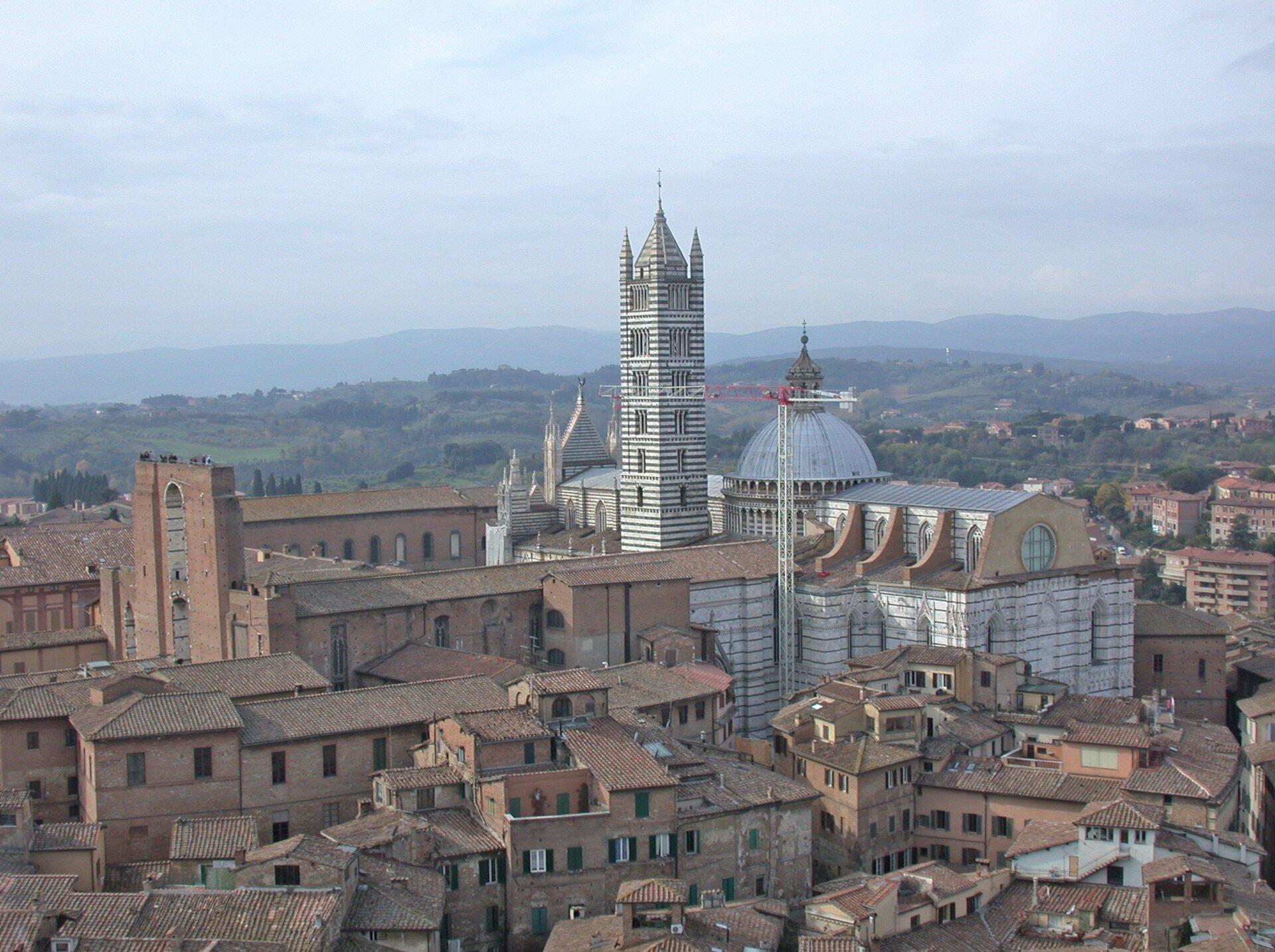 KatedrawSienie wzniesiona została wlatach 1229-1263. Nawa główna ma długość 89 miszerokość 24 m. Stojącą nieopodal dzwonnicę ukończono w1313 r. Miała wysokość 77 m. Budowę kopuły owysokości całkowitej 48 mrazem ztzw. latarnią (nadbudówka nad kopułą) rozpoczęto w1263 r., aukończono w1385 r. (latarnię dopiero w1667 r.).W1339 r. rozpoczęto wielką rozbudowę, wktórej istniejąca katedra miała stać się jedynie nawą poprzeczną przyszłej monumentalnej budowli (jej wymiary to 50 mdługości i30 mszerokości). Czarna śmierć iwywołany przez nią kryzys spowodowały przerwanie prac w1357 r.; resztki zamierzenia widać do dzisiaj. KatedrawSienie wzniesiona została wlatach 1229-1263. Nawa główna ma długość 89 miszerokość 24 m. Stojącą nieopodal dzwonnicę ukończono w1313 r. Miała wysokość 77 m. Budowę kopuły owysokości całkowitej 48 mrazem ztzw. latarnią (nadbudówka nad kopułą) rozpoczęto w1263 r., aukończono w1385 r. (latarnię dopiero w1667 r.).W1339 r. rozpoczęto wielką rozbudowę, wktórej istniejąca katedra miała stać się jedynie nawą poprzeczną przyszłej monumentalnej budowli (jej wymiary to 50 mdługości i30 mszerokości). Czarna śmierć iwywołany przez nią kryzys spowodowały przerwanie prac w1357 r.; resztki zamierzenia widać do dzisiaj. Źródło: MM, domena publiczna.