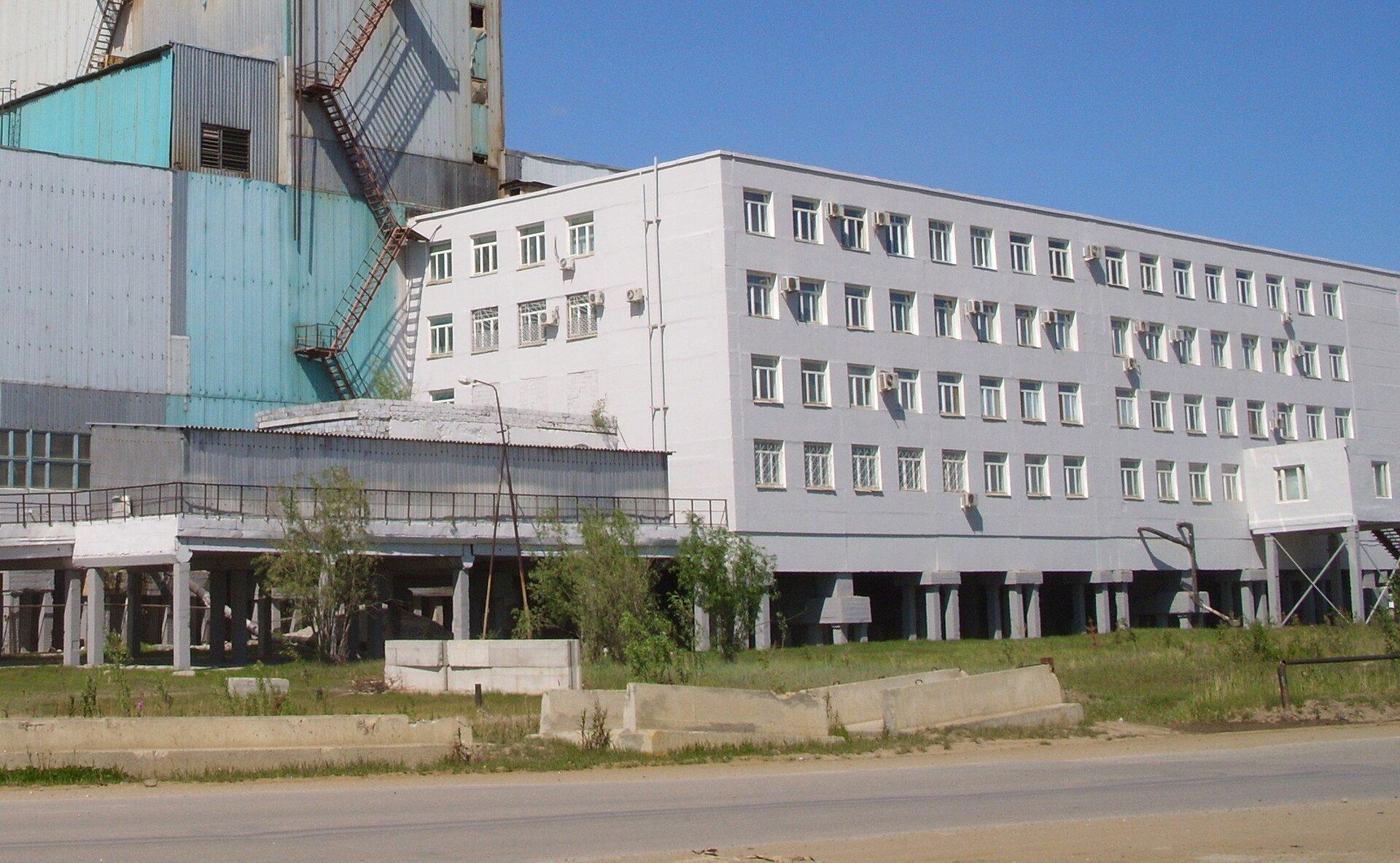 Fotografia prezentuje trzypiętrowy, biały, betonowy budynek zwieloma oknami. Budynek wzniesiono na betonowych palach wbitych wziemię.