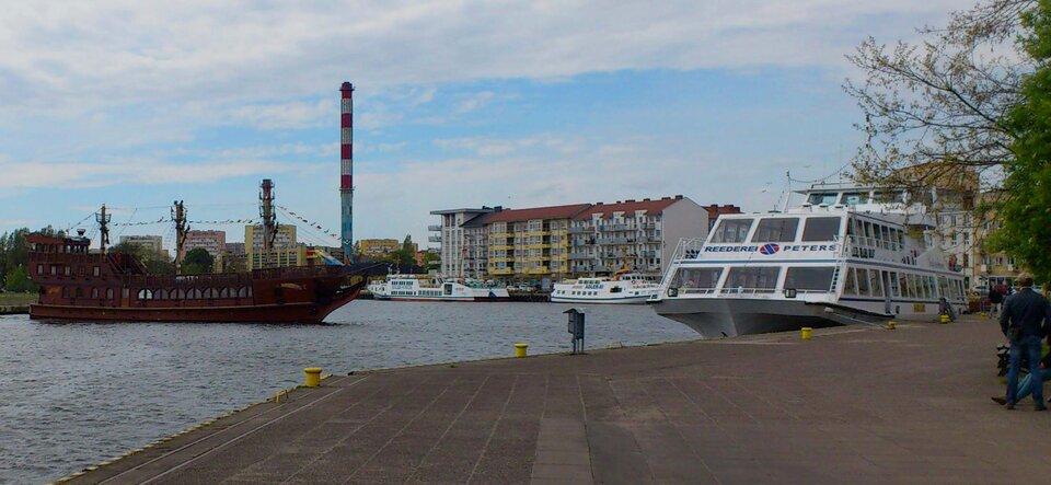 Na zdjęciu betonowe nabrzeże, zacumowane statki. Wtle zabudowania wielorodzinne.