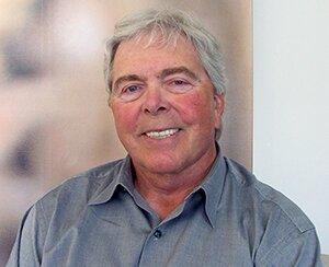 Fotografia przedstawia uśmiechniętego mężczyznę osiwych włosach.