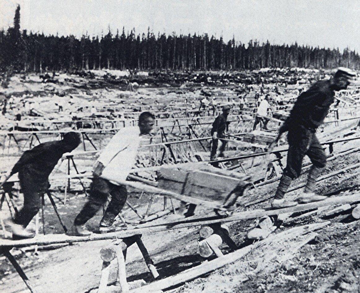Budowa Kanału Białomorskiego Zdjęcie przedstawia budowę Kanału Białomorskiego. Kanał łączył Morze Bałtyckie iMorze Białe.Był efektem pracy 170 tysięcy więźniów wlatach 1930-1933. Źródło: Budowa Kanału Białomorskiego, 1932, fotografia, domena publiczna.