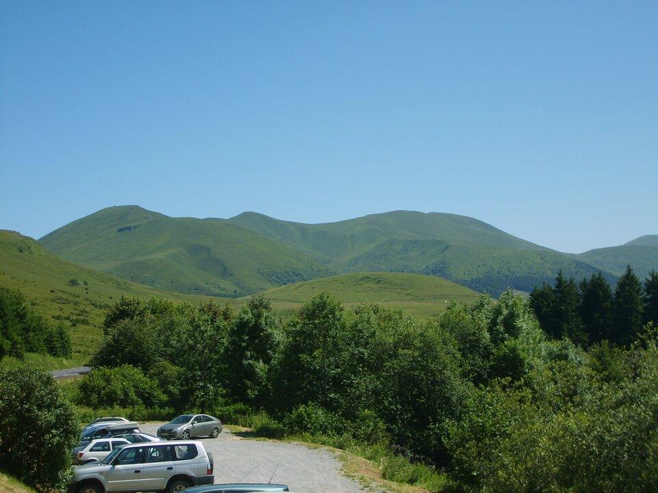 Na zdjęciu pasmo górskie ołagodnych stokach porośniętych trawą.