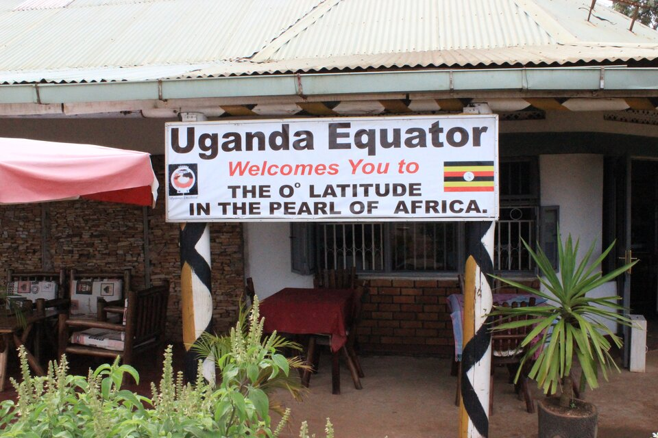 Na zdjęciu biała tablica znapisami wjęzyku angielskim zawieszona pod daszkiem, przed wejściem do budynku.