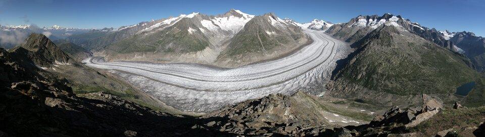 Na zdjęciu góry. Ośnieżone szczyty, brak roślinności. Zprawej strony dolina. Spomiędzy pasm górskich wypływa lodowiec. Szeroki pas zmrożonego śniegu, jęzor lodowca płynie wdół, zataczając szeroki łuk wlewą stronę. Wtle wąski pas niebieskiego nieba.