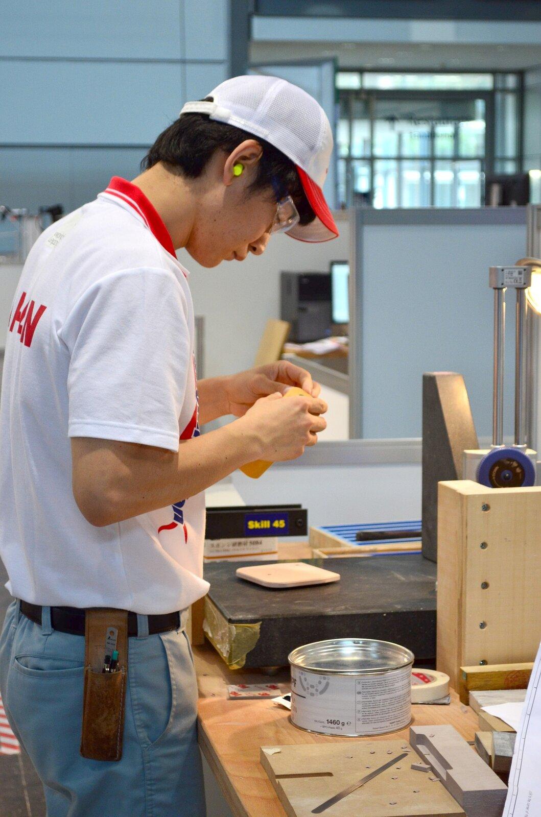 na zdjęciu widać młodego człowieka pracującego wdrewnie