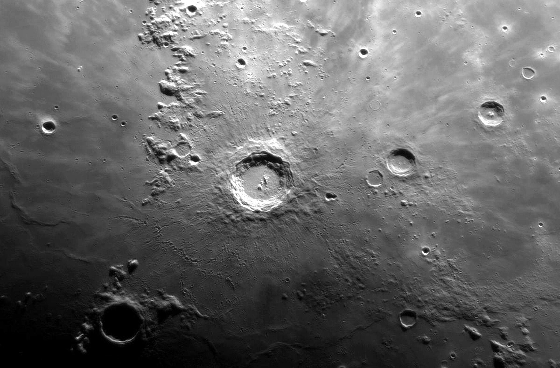 Ilustracja przedstawia kratery na Księżycu. Powierzchnia Księżyca szara, niejednolita Barwa od jasno szarego do ciemnoszarego, prawie czarnego. Miejscami widoczne kratery różnej wielkości. Po środku znajduje się największy, najjaśniejszy krater.
