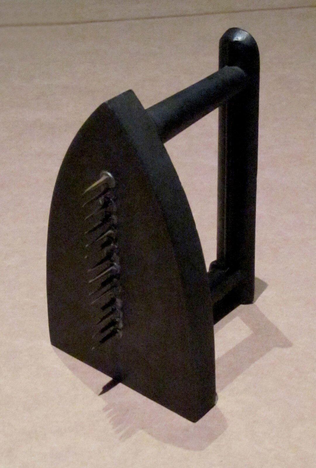 """Ilustracja przedstawia dzieło Mana Raya pt. """"Dar"""". Rzeźba jest jedną ze słynnych ikon ruchu surrealistycznego. Składa się zpłaskiego czarnego żelazka, które zostało przekształcone wniefunkcjonalny przedmiot poprzez dodanie rzędu czternastu gwoździ.."""