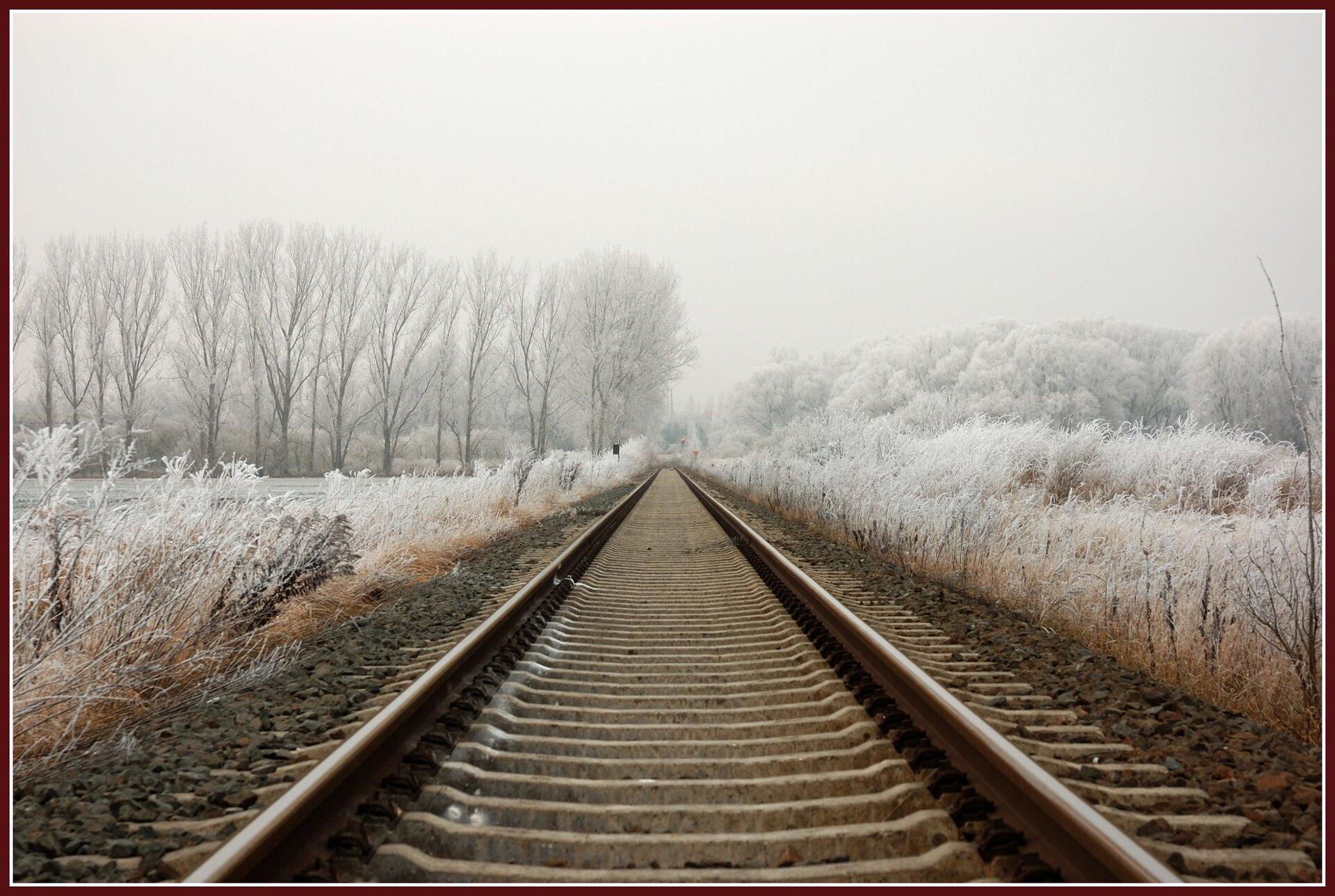 Ilustracja przedstawia tor kolejowy. Prowadzi, aż po horyzont gdzie widać drzewa pokryte śniegiem. Prowadzi on przez łąkę ilas. Pora roku przedstawiona na zdjęciu to zima. Niebo pokryte jest jasnymi białymi chmurami.