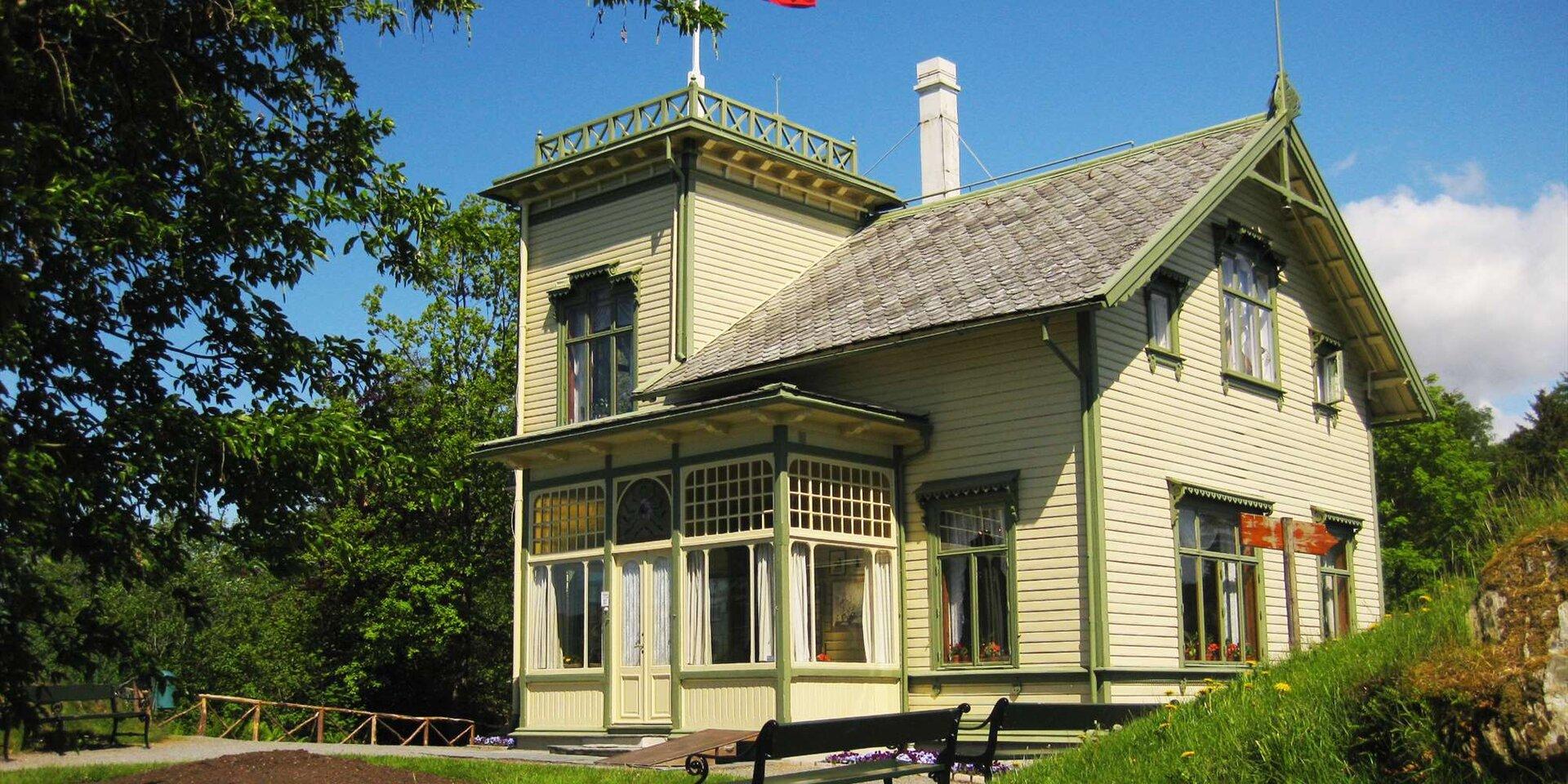 Ilustracja przedstawia dom Edvarda Griega. Widoczna jest drewniana chata wśród zieleni.