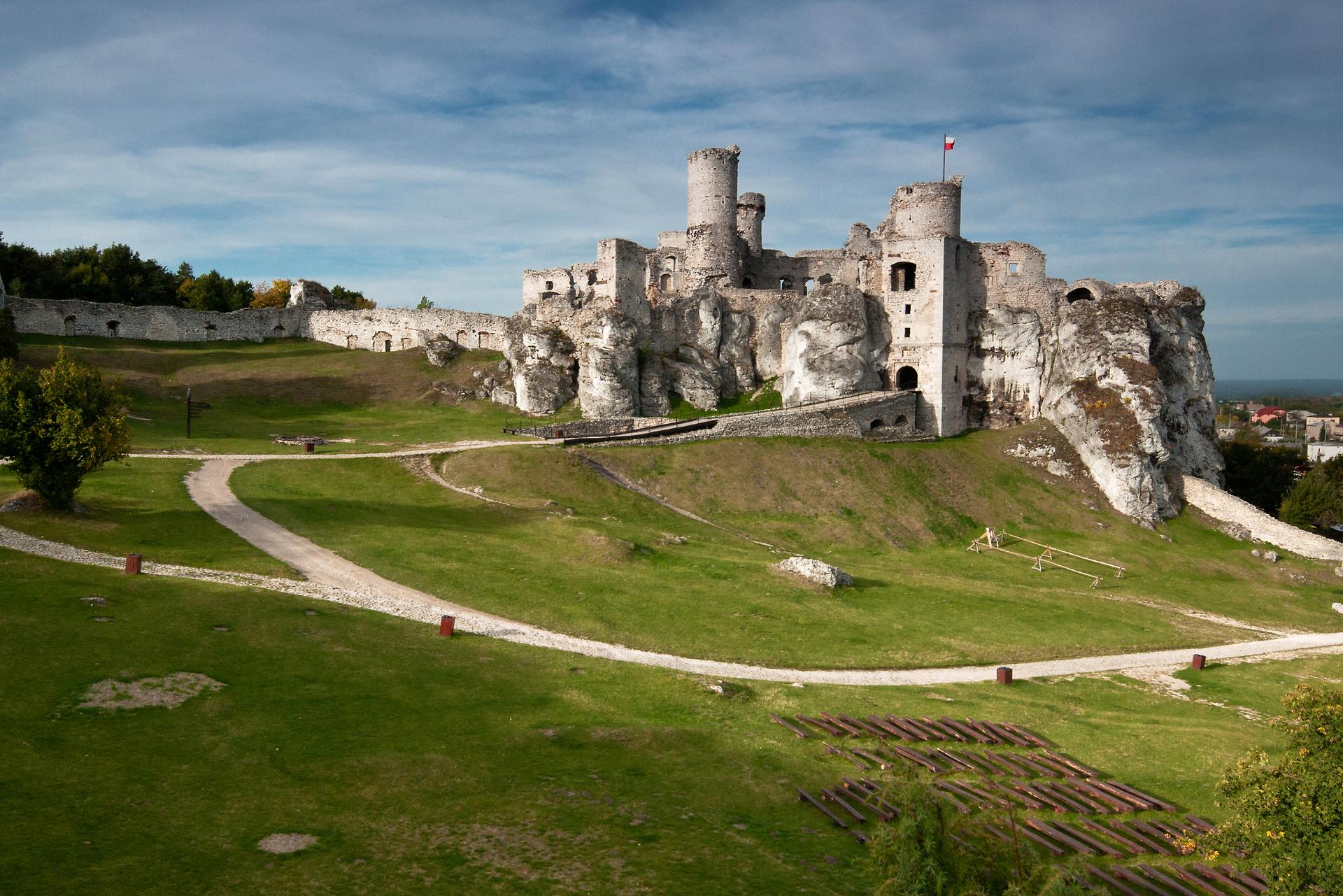 Fotografia prezentuje ruiny zamku Ogrodzieniec, umiejscowione na wzgórzu, do którego prowadzi kręta droga.