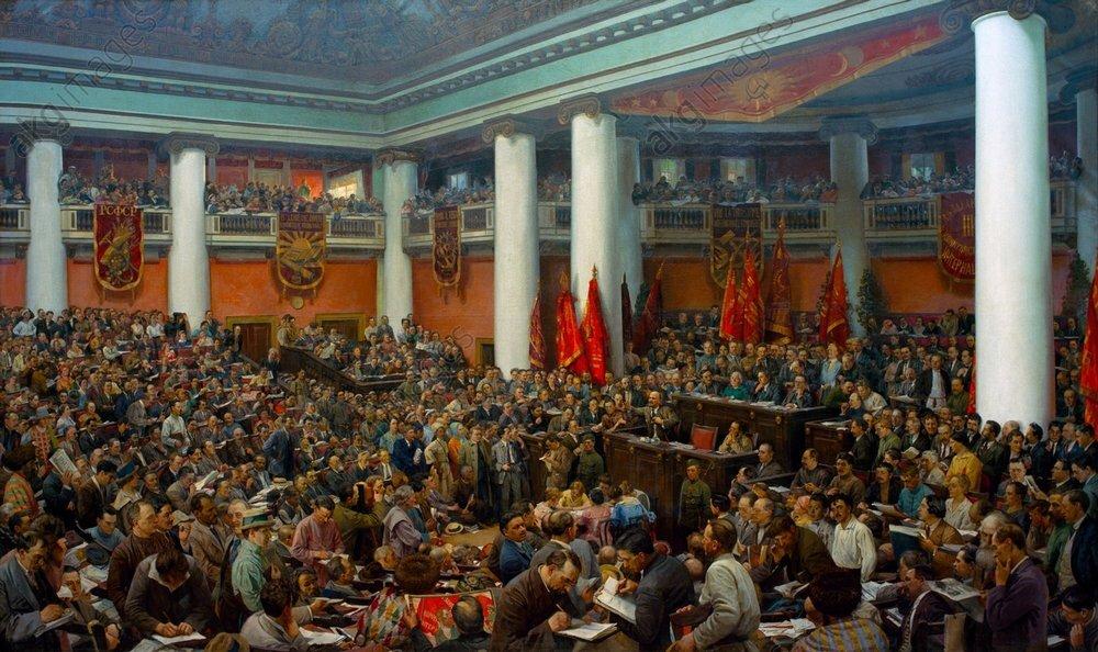 Ilustracja przedstawia przemówienie Lenina wradzieckim parlamencie. Większość ludzi słucha przemówienia, inni czytają gazety lub rozmawiają ze sobą. Wsali widać kolumny podtrzymujące strop, flagi oraz zwisające zbalkonu sztandary