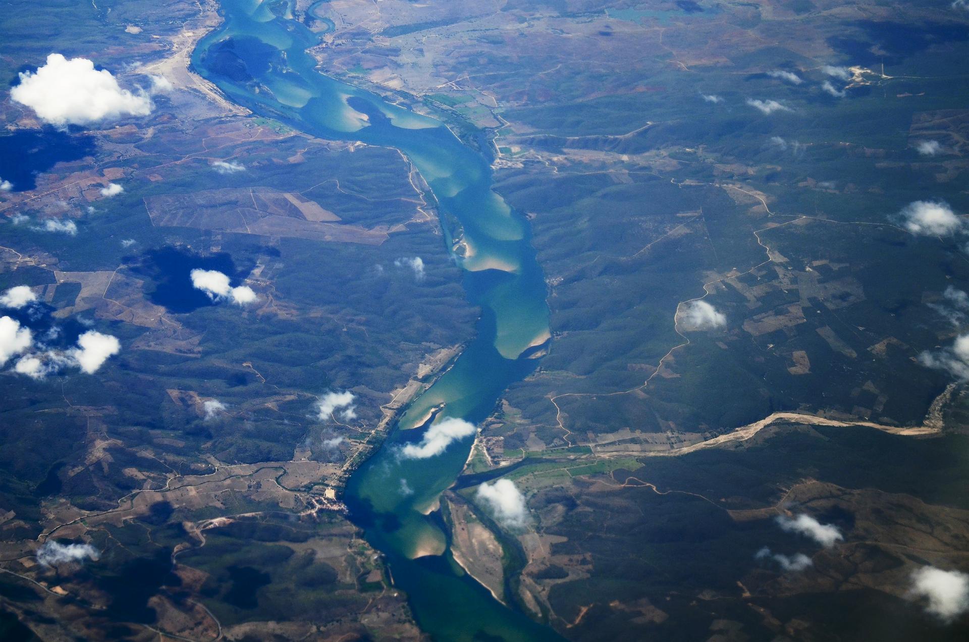 Na fotografii wykonanej zlotu ptaka rozległa równina porośnięta lasami. Środkiem płynie rzeka. Płynie spokojnie, widoczne łachy piasku. Ponad przedstawionym obszarem płyną białe chmury.