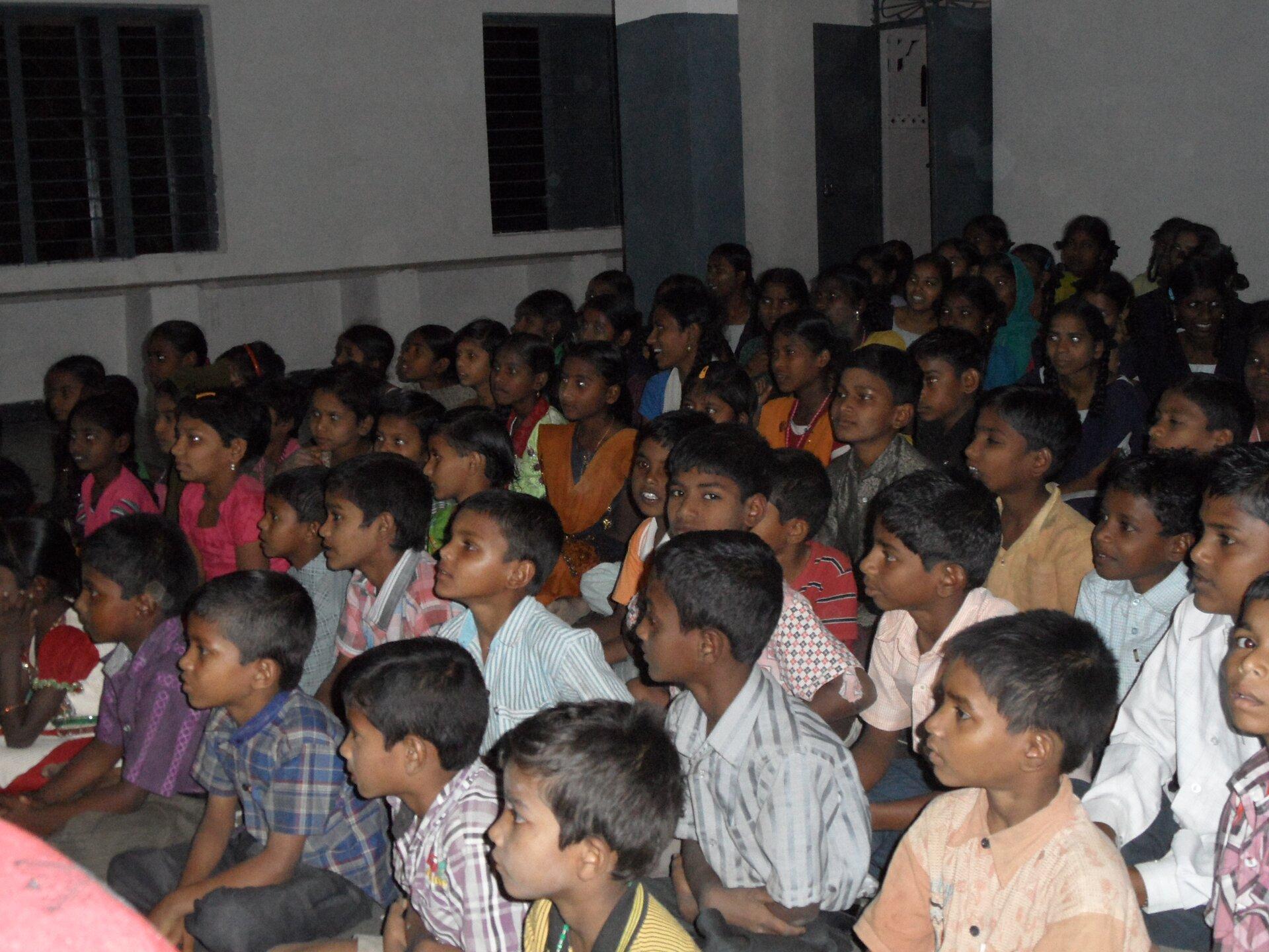 Na zdjęciu duża grupa dzieci siedzących ciasno obok siebie wsali.