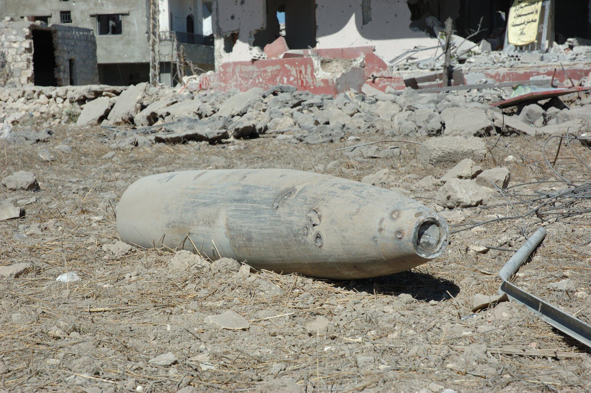 Fotografia prezentuje dużych rozmiarów pocisk leżący na ziemi , dookoła gruzy budynku