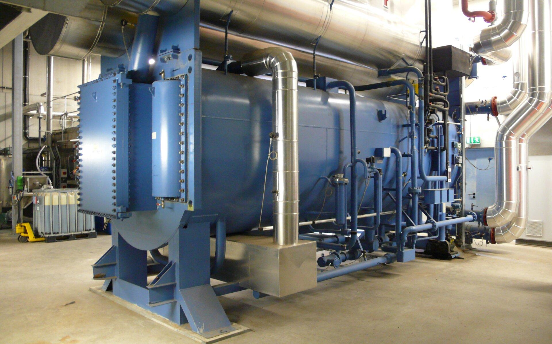 Na zdjęciu duży metalowy zbiornik, dookoła rury różnej grubości.