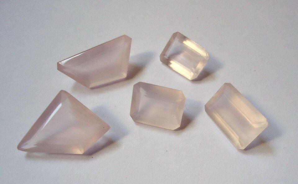 Zdjęcie przedstawia pięć oszlifowanych kawałków kwarcu różowego omlecznoróżowej barwie. Trzy mają szlif szmaragdowy, czyli prostokątny, zaś dwa są nieregularnymi pięciobokami. Wszystkie kamienie leżą obok siebie na białym tle.