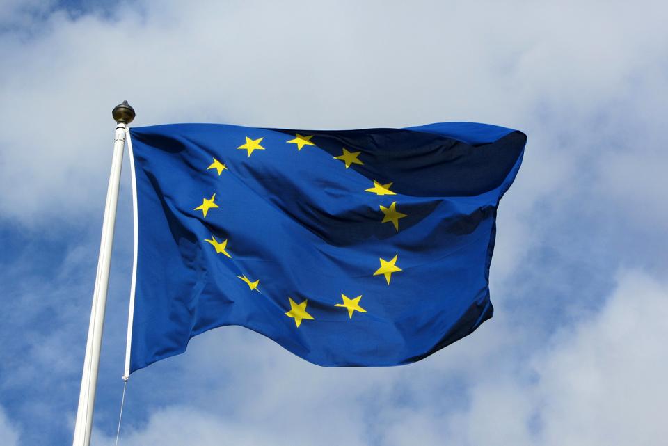 Zdjęcie przedstawia flagę Europy zawieszoną na maszcie. Maszt po lewej stronie zdjęcia. Flaga powiewa skierowana wprawo. Na granatowym tle 12 pięcioramiennych gwiazdek. Gwiazdy ułożone są wokrąg.