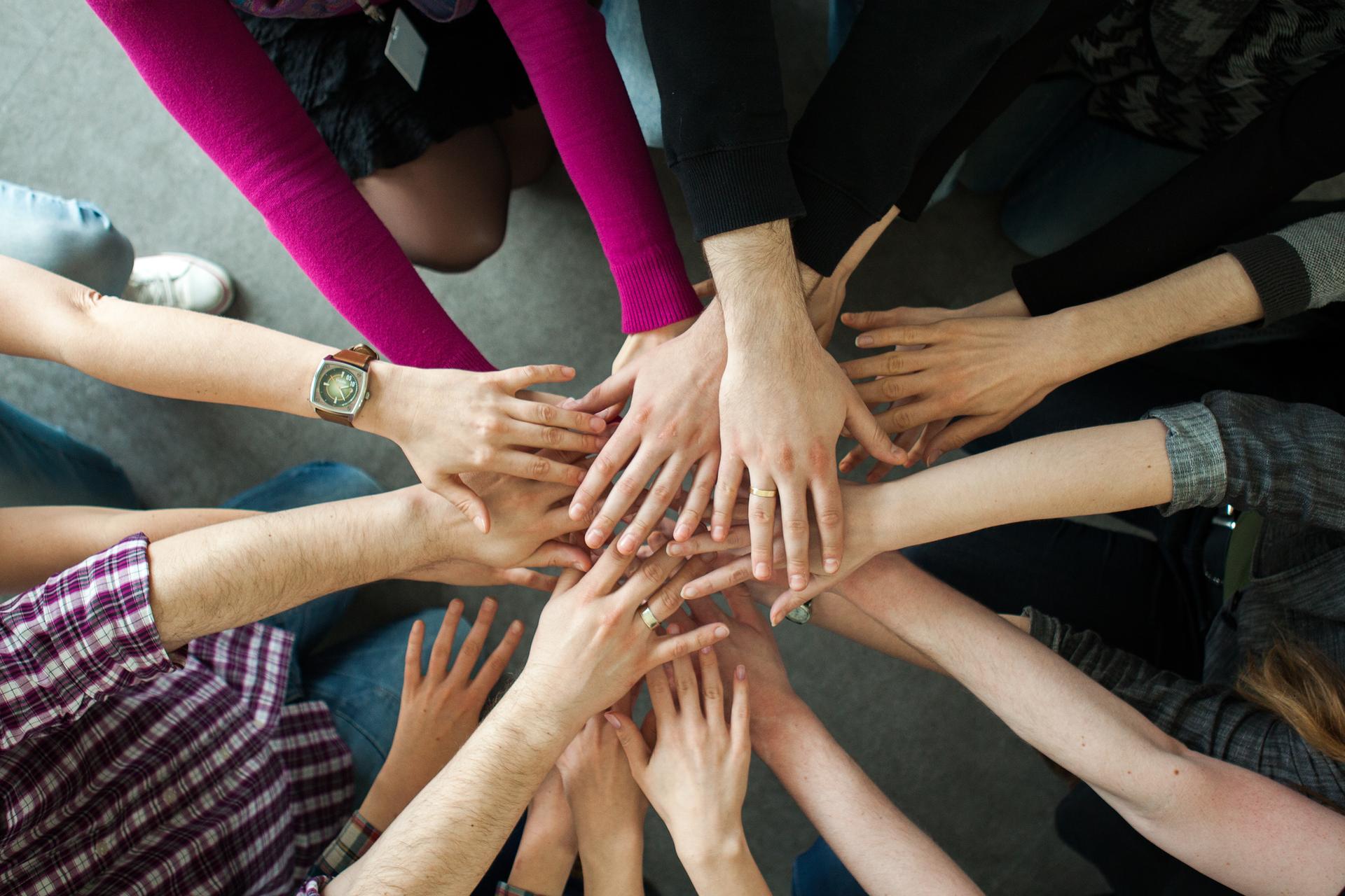 Kolorowe zdjęcie przedstawia osiem osób stojących wkręgu. Zbliżenie na ręce osób. Dłonie ułożone są jedna na drugiej. Ręce tworzą promienie.