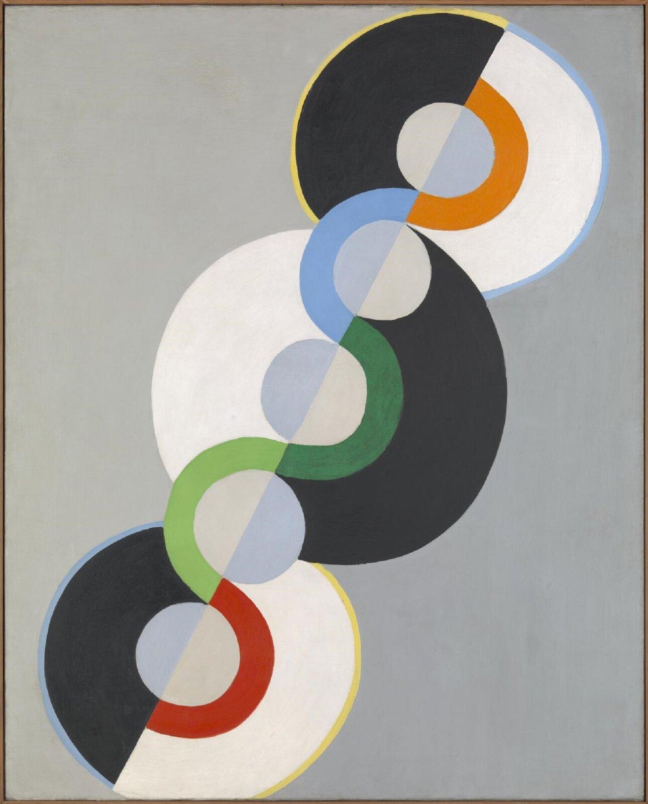 """Ilustracja przedstawia obraz """"Nieskończony Rytm"""" autorstwa Roberta Delaunaya. Wcentrum dzieła, na szarym tle namalowana została kompozycja składająca się ztrzech, ułożonych po skosie, czarno-białych, dużych kół, na których tle znajdują się mniejsze, pomalowane szarą ijasno-niebieską farbą kółka. Pomiędzy nimi przebiega pofalowana linia kolorowego pasa. Wszystkie elementy tworzą jeden ułożony po skosie kształt, wzdłuż którego przebiega skośna linia podziału, dzieląca kształt na dwie, równe części odróżniające się od siebie jedynie kolorami. Lewe połowy dużych górnych idolnych kół są czarne, natomiast prawe są białe. Środkowe koło na odmianę ma białą lewą połowę aprawą czarną. Trzy małe kółka mają jasno-niebieskie lewe połowy aprawe szare, natomiast dwa pozostałe kółka po lewej są szare apo prawej jasno-niebieskie. Obraz skomponowany jest dynamicznie po skosie. Wrażenie ruchu potęguje umieszczona wcentrum kompozycji gruba, falująca, pomarańczowo-niebiesko-zielono-czerwona linia."""