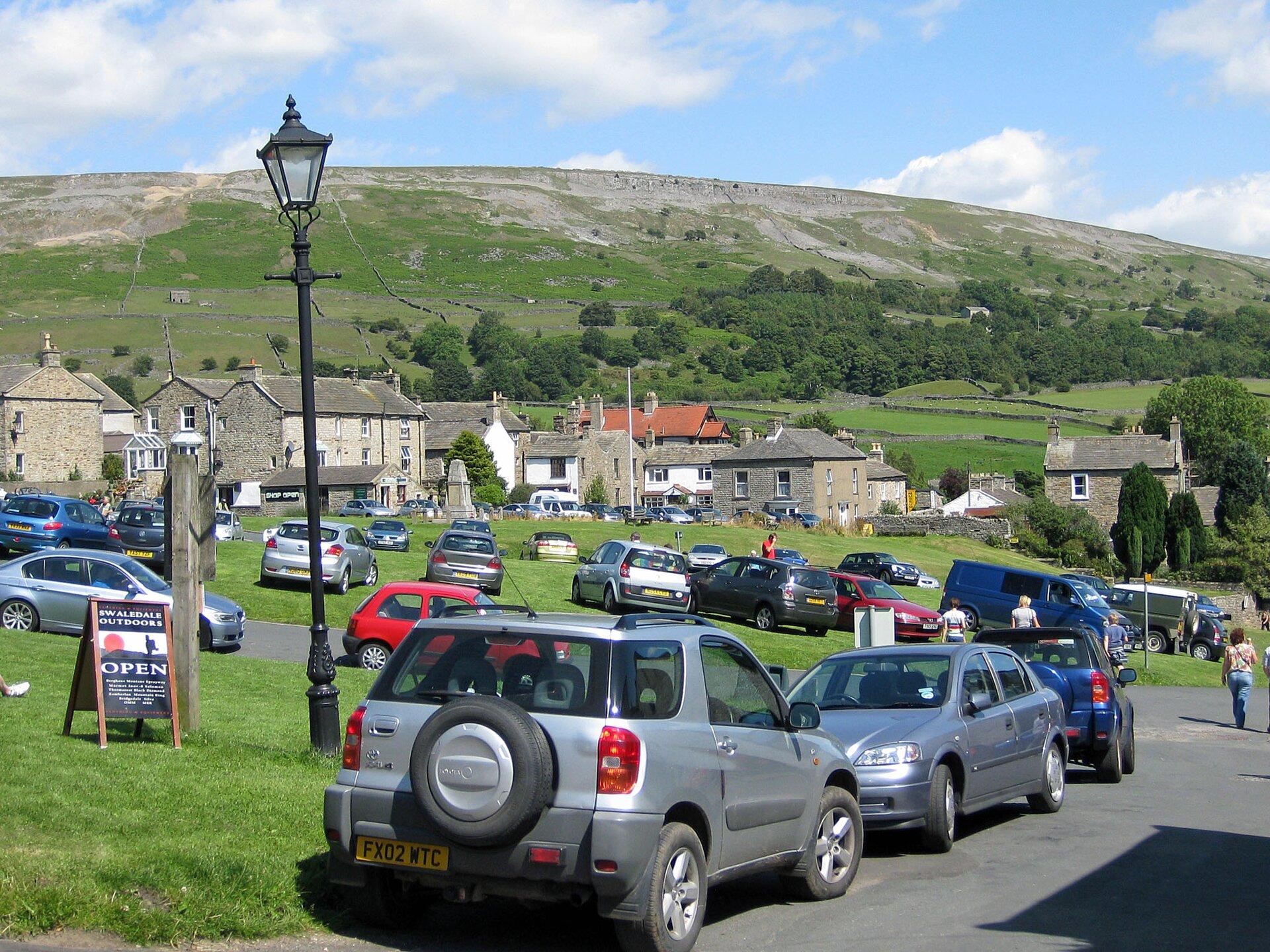 Na zdjęciu wieś. Na pierwszym planie duża liczba zaparkowanych samochodów. Wzdłuż ulicy ina trawnikach. Wtle zabudowania, kamienne domy ze spadzistymi dachami. Dalej teren górski. Łagodne stoki pokryte drzewami.