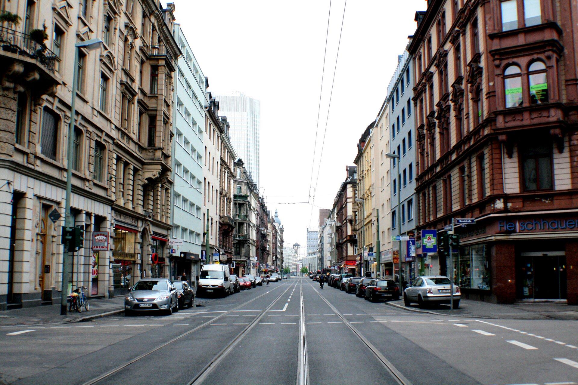 Ilustracja przedstawia ulicę miasta. Jest to prosta jezdnia zwidocznymi dwoma torami tramwajowymi. Przy drodze stoją auta. Po obu stronach są wielopiętrowe kamienice oróznych kolorach elewacji. Nad jezdnią rozciąga się trakcja elektryczna dla tramwajów. Wtle widać wieżowiec ijasne niebo.