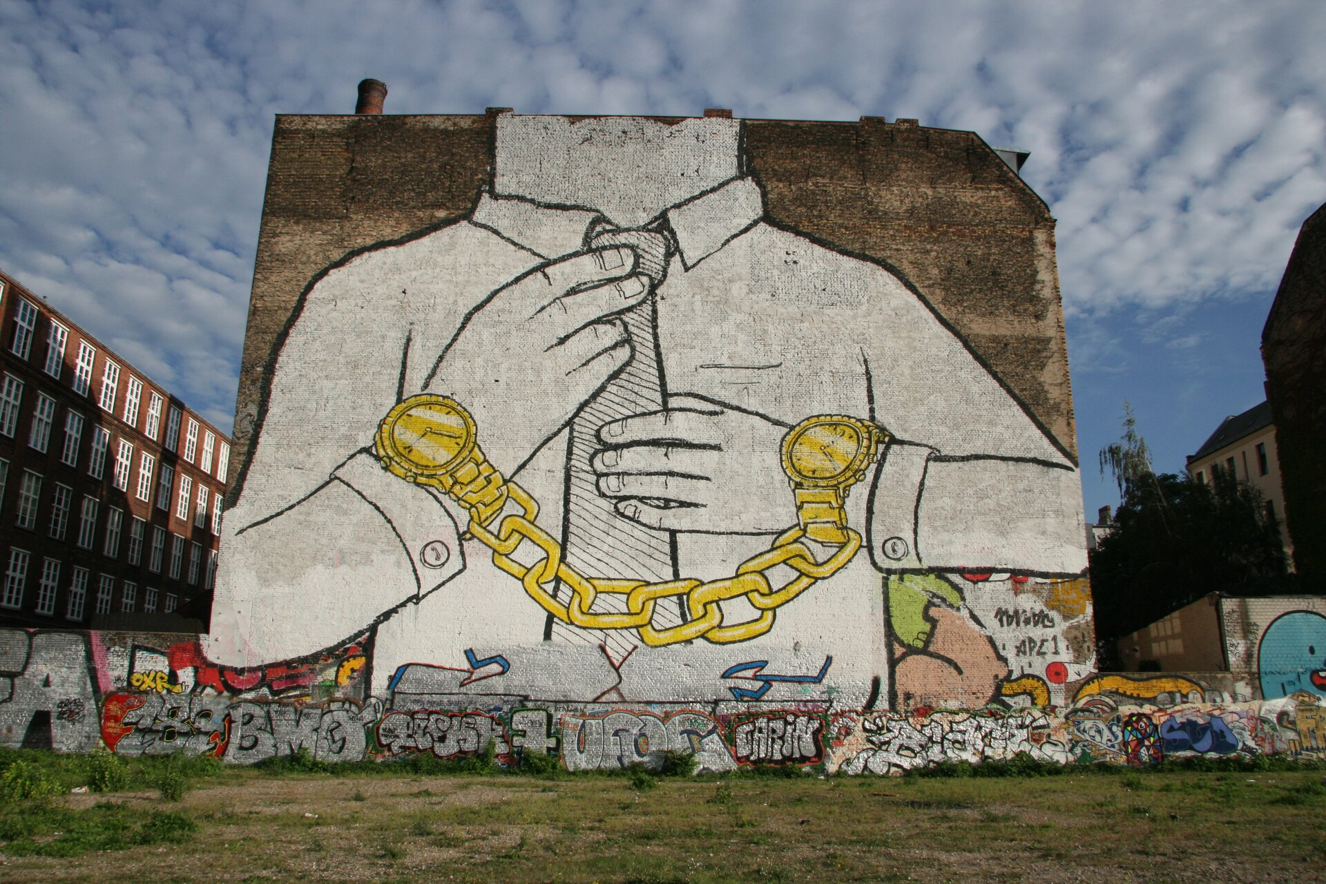 Ilustracja przedstawia czarno-biały street art BLU. Ukazuje ścianę, na której namalowany jest fragment mężczyzny wbiałej koszuli ikrawacie oraz złotych zegarkach na rękach, które połączone są złotym łańcuchem. Zegarki przypominają kajdanki. Na dole znajduje się szereg grafficiarskich napisów.