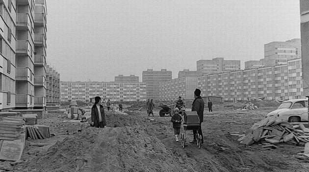 Fotografia czarno-biała przedstawiająca wielopiętrowe bloki zwielkiej płyty. Plac budowy, piach, materiały budowlane apomiędzy nimi mieszkańcy spacerujący zdziećmi.