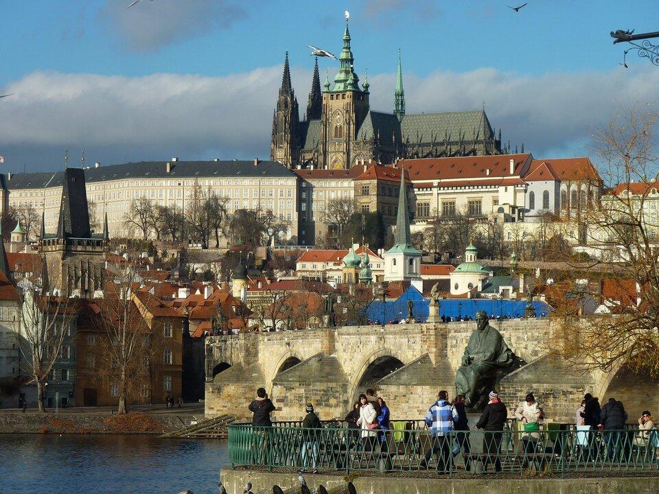 Na zdjęciu stara, zabytkowa zabudowa, na pierwszym planie rzeka ikamienny most, dalej zwarta zabudowa miejska – kamienice ikościoły, powyżej zamek zkilkoma wieżami.