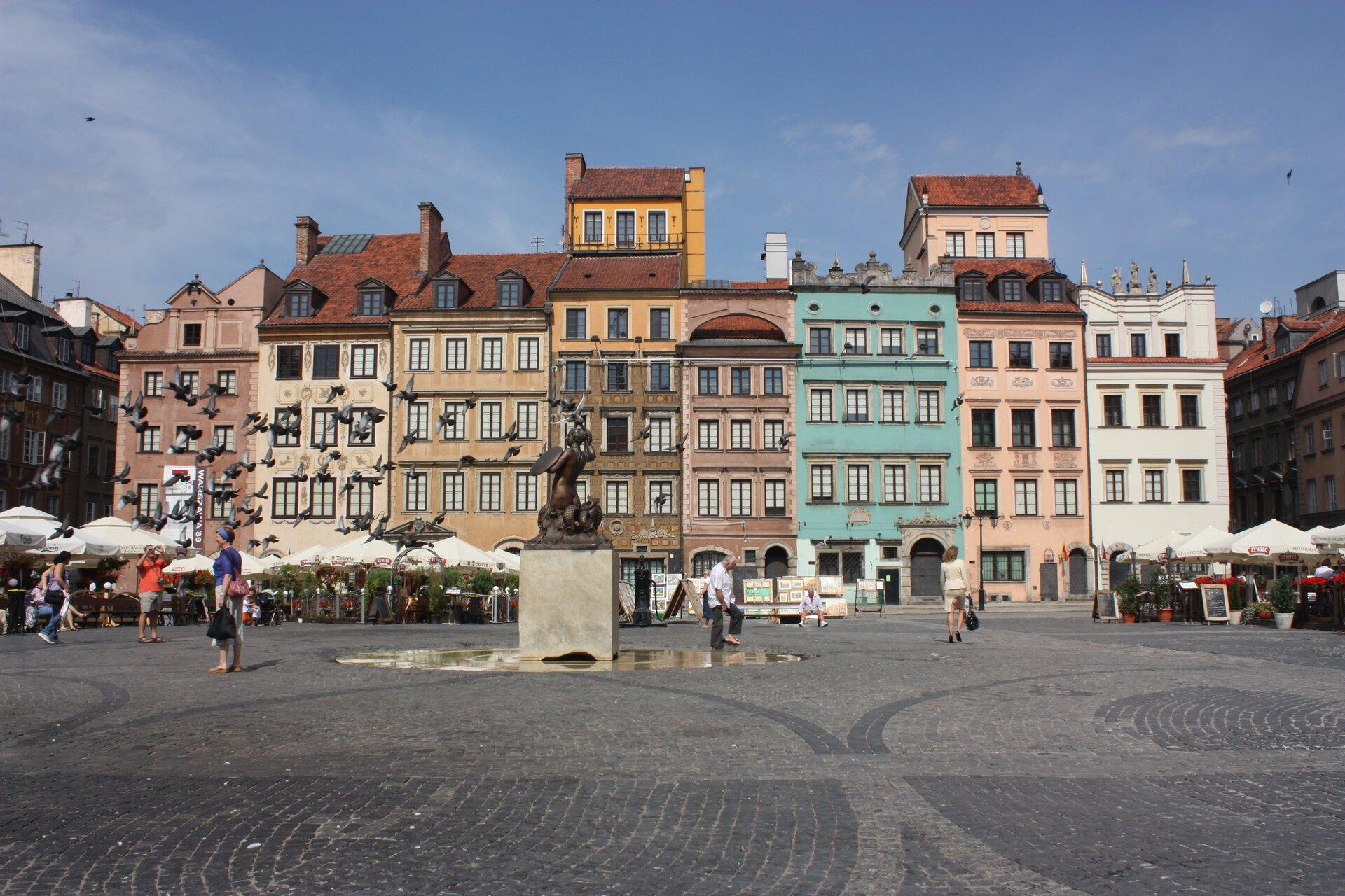 Na zdjęciu kilka kolorowych kamienic zczerwonymi dachami. Przed nimi plac wyłożony kostką brukową. Na środku rzeźba, Syrenka ztarczą. Przechodnie, kawiarniane ogródki, parasole, gołębie.