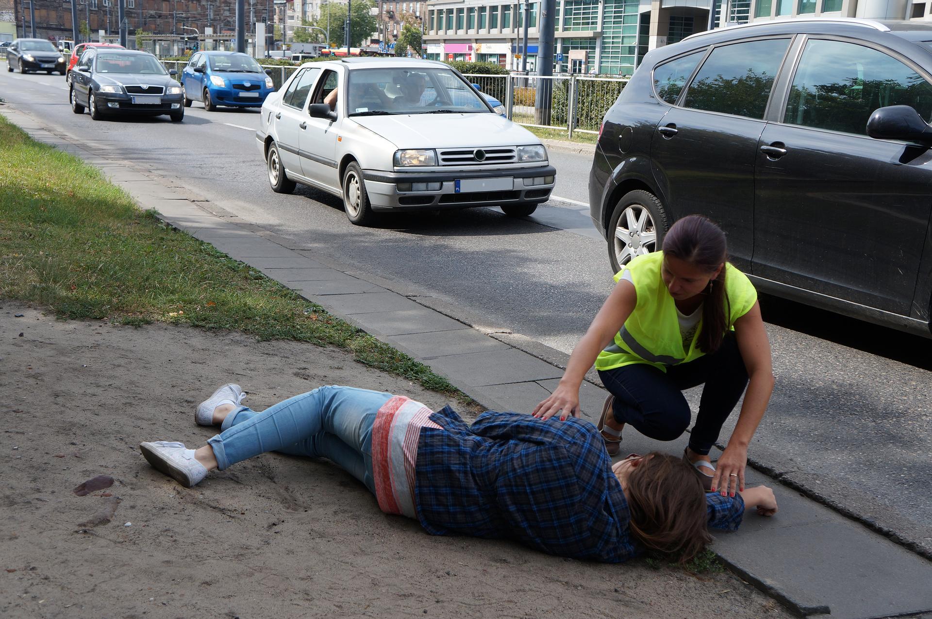 Zdjęcie przedstawia osobę wkamizelce odblaskowej klęczącą leżącym na skraju ulicy poszkodowanym. Tuż obok jezdnią jedzie sznur samochodów.