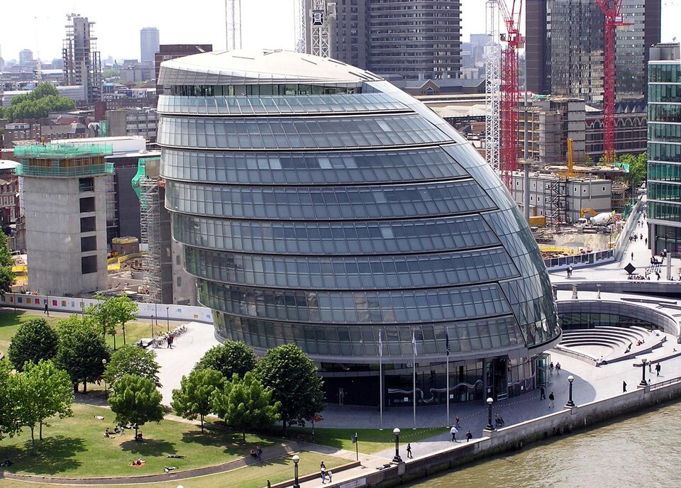 Zdjęcie przedstawia dwunastopiętrowy oszklony budynek londyńskiego Ratusza, którego każde piętro jest nieznacznie przesunięte wlewo względem poprzedniego, przez co budowla sprawia wrażenie mocno przekrzywionego jajka, albo podobnej do wielkiego żagla.