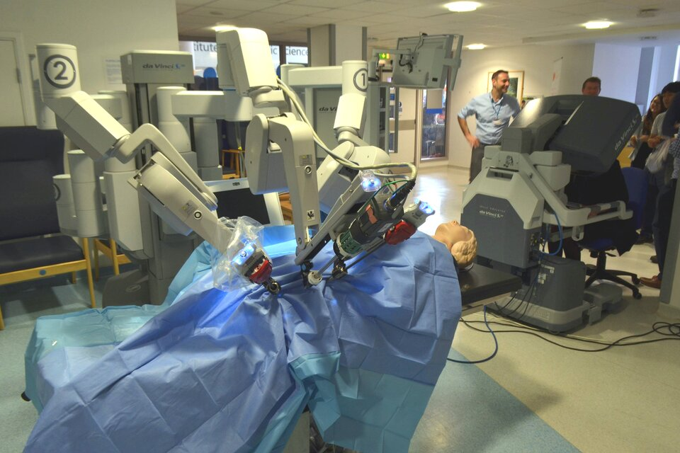 Na zdjęciu system robota medycznego. System składa się zdwóch odrębnych części – konsoli chirurgicznej oraz robota medycznego, posiadającego kilka ramion. Przy konsoli stoją ludzie. Na łóżku operacyjnym leży manekin, przykryty niebieskim prześcieradłem. Wtle inne urządzenia medyczne.