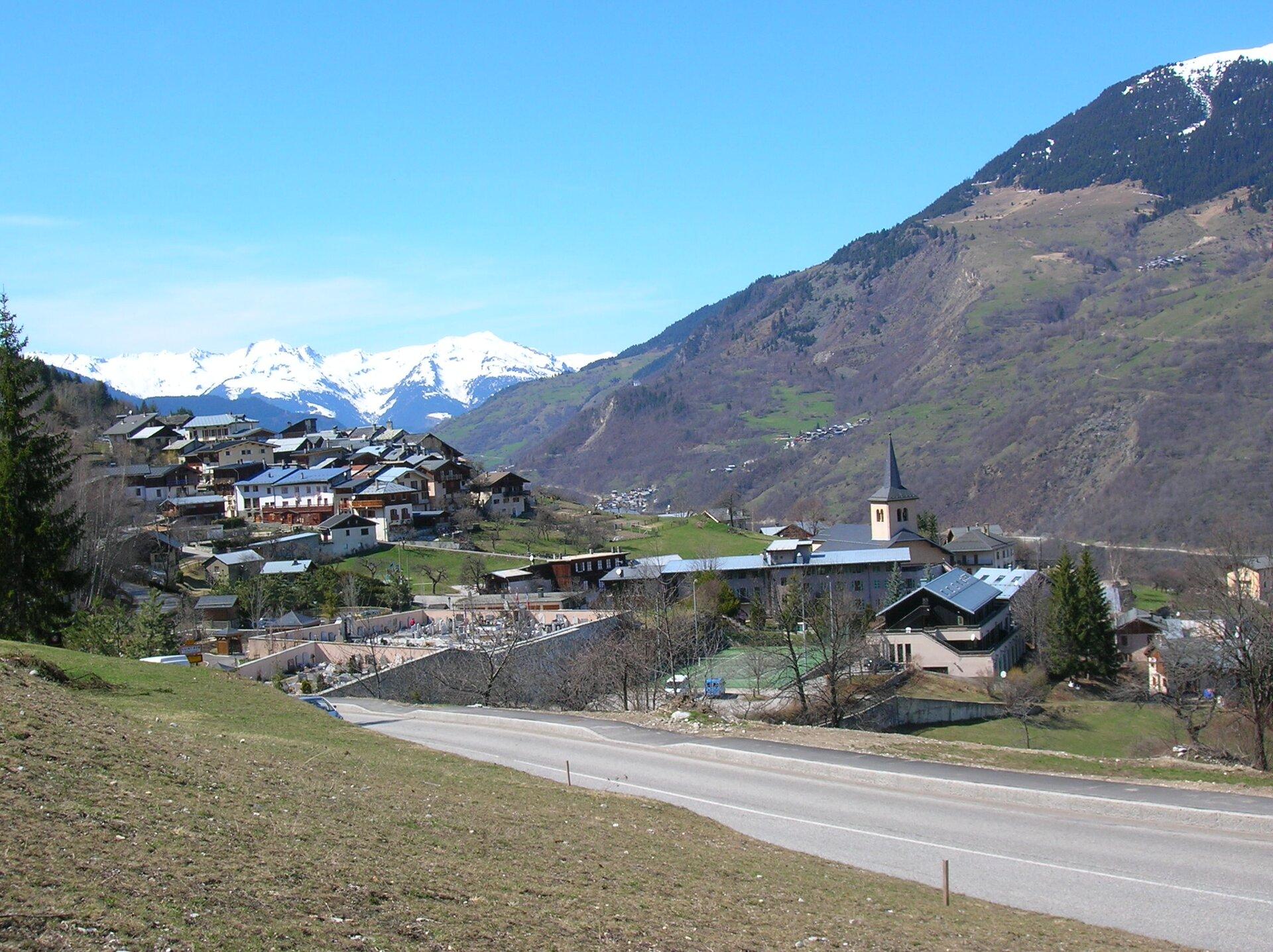 Na zdjęciu miejscowość górska, na pierwszym planie łagodny stok, brunatna ziemia, brak roślinności. Wtle wysokie, ośnieżone szczyty.