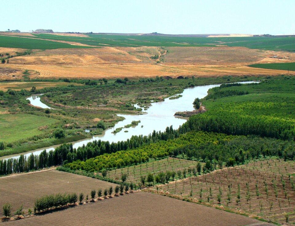 Na zdjęciu pola uprawne nad rzeką. Wtle pagórkowaty teren.
