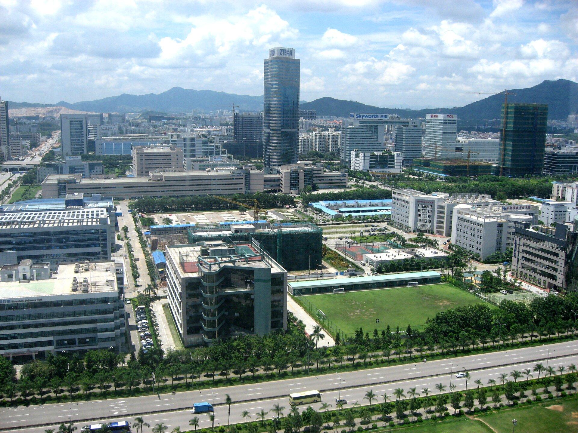 Na zdjęciu nowoczesna zabudowa mieszkaniowa ibiurowa. Liczne tereny zielone. Wtle góry.