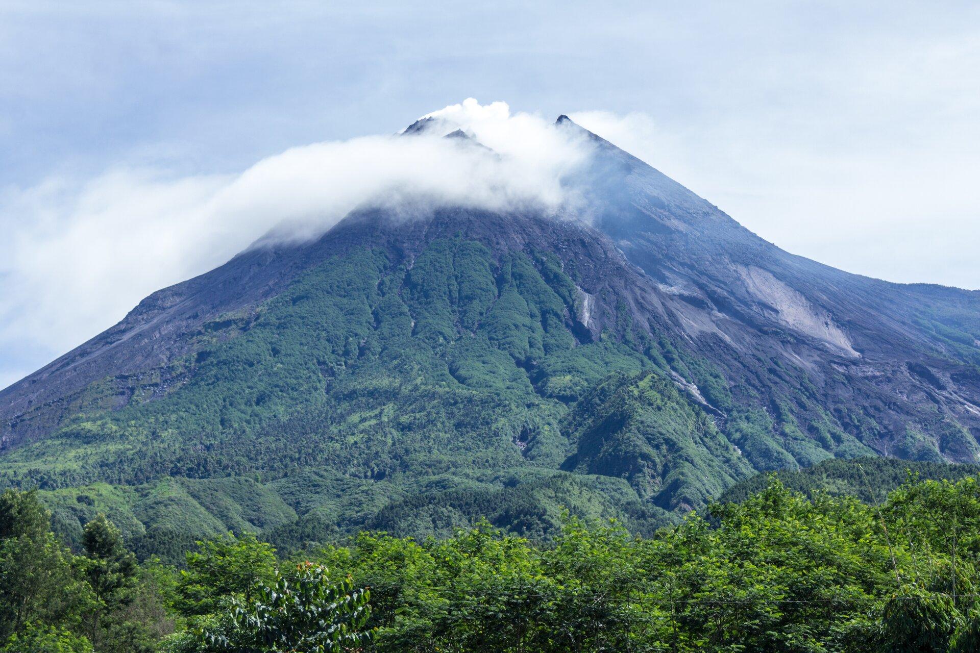 Zdjęcie pojedynczego wierzchołka góry porośniętego bujną roślinnością. Góra wkształcie stożka. Na pierwszym planie ustóp góry las liściasty. Na szczycie góry biały dym wydobywa się zwnętrza góry. Wtle błękitne niebo.