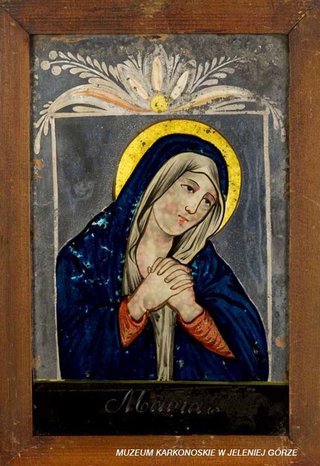 """Ilustracja przedstawia obraz """"Matka Boska Bolesna"""". Postać Maryi jest ubrana wczerwoną suknię, biały welon igranatowy płaszcz. Ma złożone ręce ilekko pochyloną głowę. Wokół głowy znajduje się nimb. Obrysowana jest białą linią. Wgórnej części znajduje się dekoracyjny motyw roślinny. Na dole umieszczony jest napis Maria."""