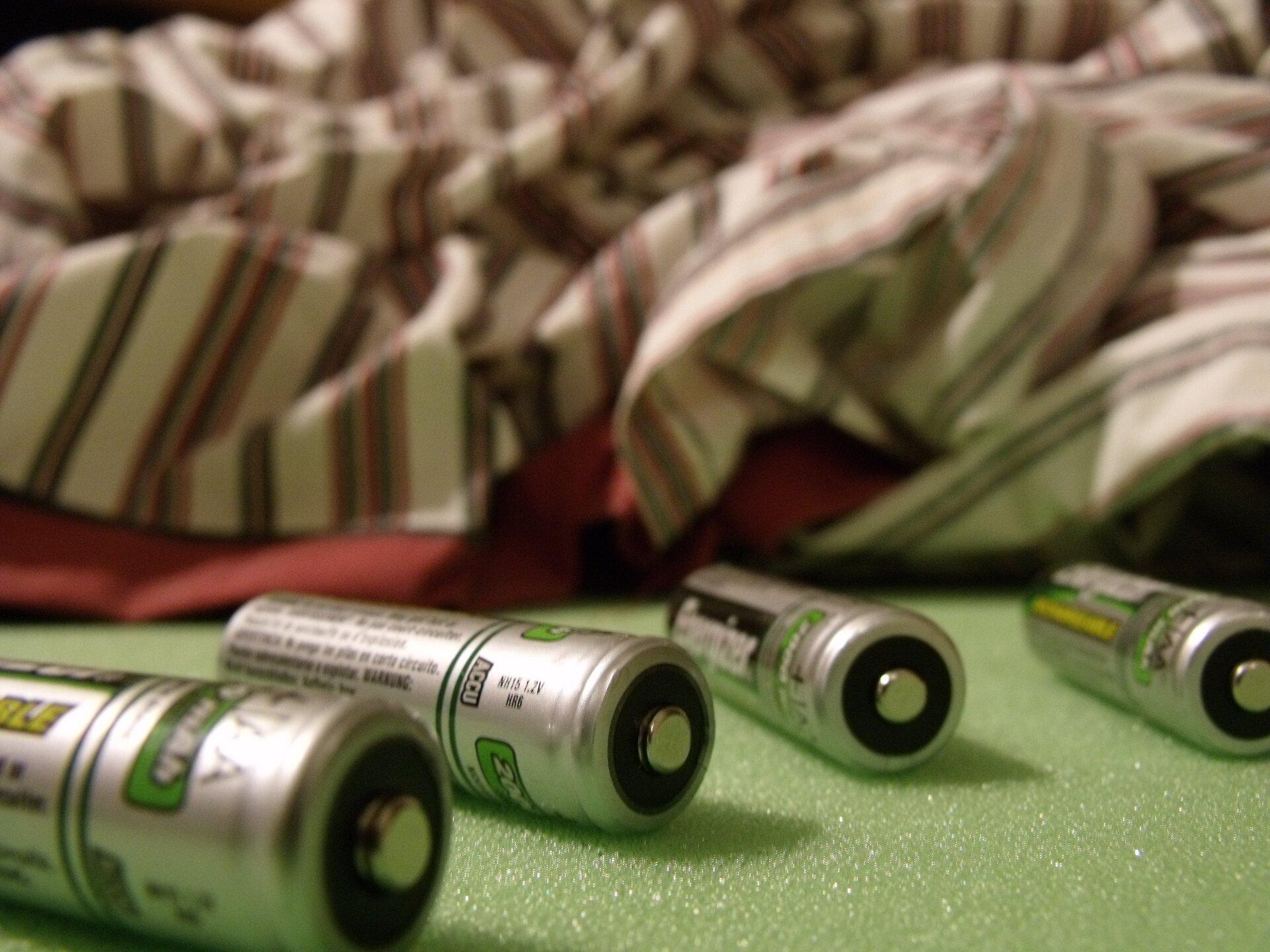 Zdjęcie przedstawia cztery akumulatorki niklowo wodorkowe typu AA, czyli popularne paluszki leżące na zielonej podkładce zgąbki. Wtle, wobszarze nieostrym zdjęcia rozłożony pasiasty materiał.