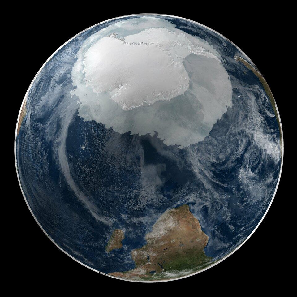 Na ilustracji kula ziemska sfotografowana zprzestrzeni kosmicznej od strony bieguna południowego. Widoczne wody wkolorze ciemnoniebieskim iżółto-zielony ląd na dole. Na górze kuli ziemskiej duża biała plama. Na środku jaśniejsza, brzegi ciemniejsze. To Antarktyda.